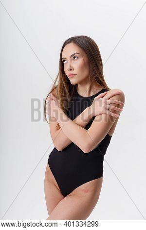 Sexy Asian Woman With Long Hair Poses In Black Lingerie On White Studio Background. Attractive Femal