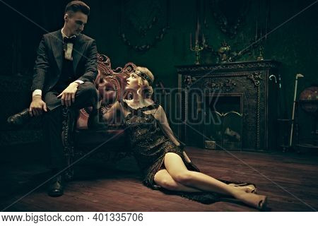 Fashion clothes, make-up and hair in luxurious retro style. Handsome man and beautiful young woman in the style of the 1920s in rich vintage apartments.
