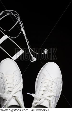 Sport Concepts. Pair Of New White Sneakers Together With Music Player And Headphones On Black Backgr