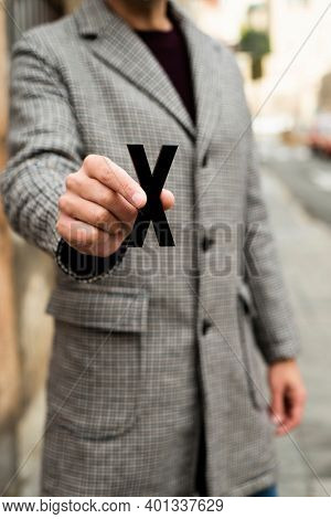 closeup of a young caucasian person standing on the street, wearing a coat, showing an X, for the third gender category