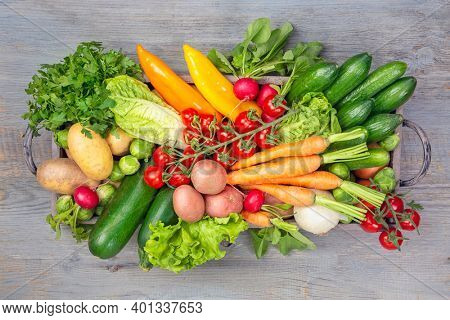 Vegetables in box on wooden background. Wooden note for your text.