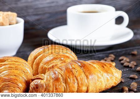 Croissants And Cup Of Coffee On A Brown Wooden Background, Breakfast With Croissants And Coffee. Mor