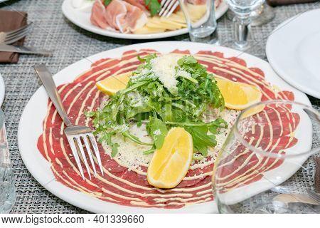 Close Up Of Italian Antipasto - Carpaccio With Arugula, Parmesan And Lemon. Mediterranean Appetizer