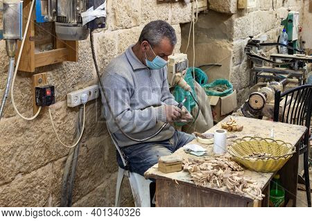 Bethlehem, Israel, December 09, 2020 : A Worker Sits And Makes Souvenirs For Sale From An Olive Tree