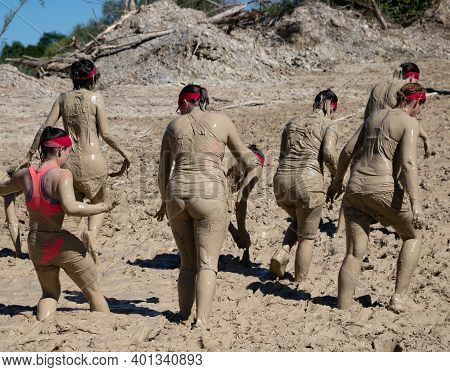 Munich, Germany - July 1, 2018: Women Crossing A Muddy Incline During Muddy Angels Breast Cancer Ben