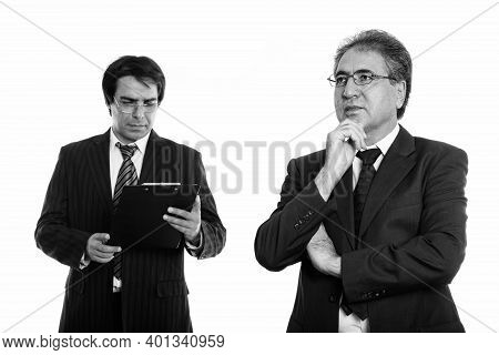 Senior Persian Businessman Thinking And Young Persian Businessman Reading On Clipboard