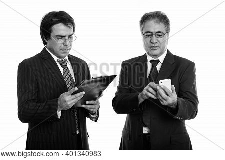 Young Persian Businessman Reading On Clipboard And Senior Persian Businessman Using Mobile Phone