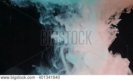 Splash Of Colored Ink In Water On Black Background. Action. Two Colors Are Mixed In Water On Isolate