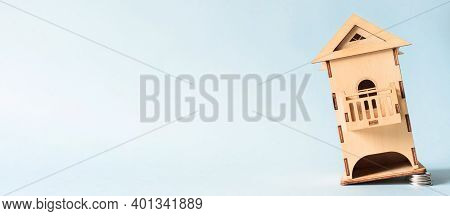 Banner Falling Miniature Wooden House, Copy Space. House Foundation Made Of Coins. Concept Of Cheap