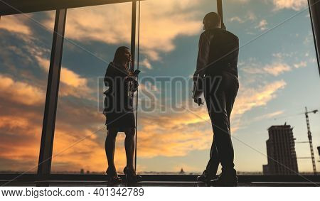 A Conversation Of Two Business Partners On The Top Of An Office Skyscraper In The Evening During A S