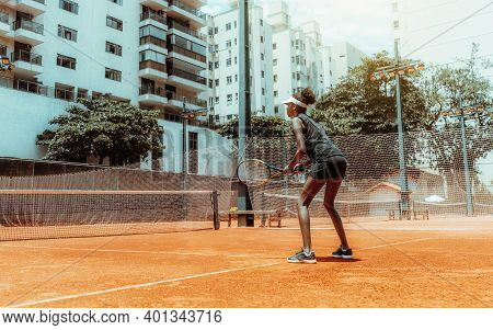 A Young Svelte African-american Female Plays Tennis Outdoors In The Training Court; A Beautiful Mixe
