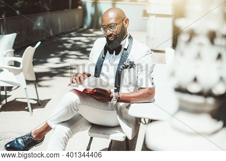 A Portrait Of A Fancy Mature Bald Bearded Black Man In Eyglasses And A White Elegant Suit With Bow-t