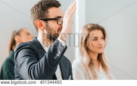 Close Up. A Young Businessman Asks A Question During A Business