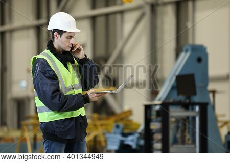 Young Man, Factory Engineer In A Work Dress And White Hard Hat Holding Smartphone And Laptop Organiz