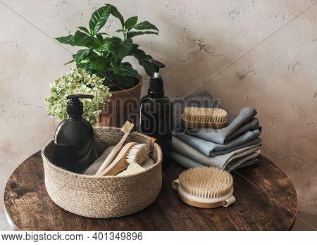 Bathroom Interior Still Life. Natural Bristle Brush, Shampoo Bottle, Towels, Flower On Dark Backgrou