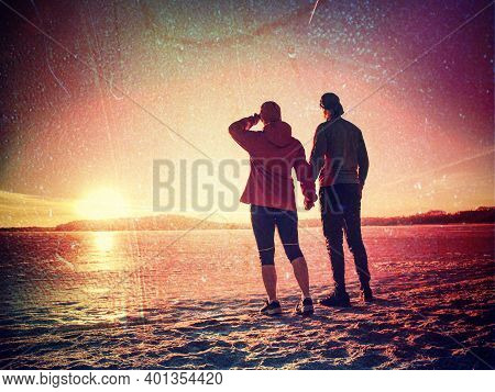 Rear View Of Loving Sports Couple Holding Hands Looking Out To Frozen Sea On Winter Beach.abstract F
