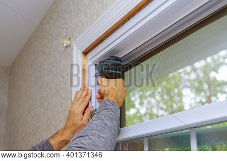 Professional Master For Installation Of New Window In House During Home Renovation Uses An Electric