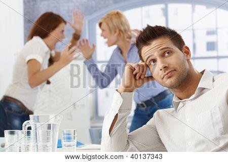 Portrait of upset businessman at meeting, businesswomen fighting in background.