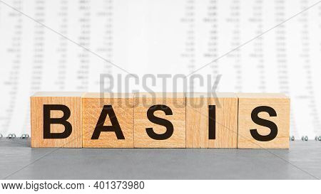 Basis Word Written On Wood Block On The Background Of Columns Of Numbers. Basis Text On Wooden Table