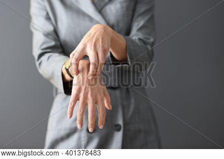 Woman In Gray Dress Scratching Her Hands Close-up. Emergence Of Allergic Diseases Concept