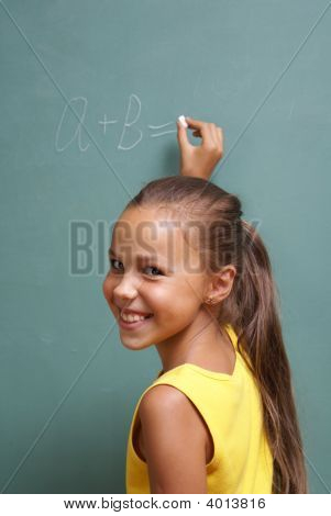School Girl Writing On Chalk Board