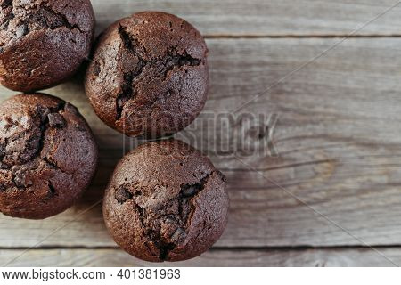 Top View Of Homemade Freshly Baked Chocolate Muffins, Keks Or Cupcakes On Wooden Table With Place Fo