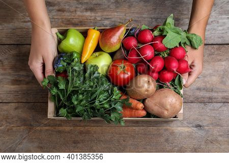 Farmer With Crate Full Of Different Vegetables And Fruits At Wooden Table, Closeup. Harvesting Time