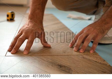 Professional Worker Installing New Parquet Flooring Indoors, Closeup