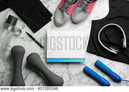 Flat Lay Composition With Sportswear, Notebook And Dumbbells On White Marble Background. Gym Workout