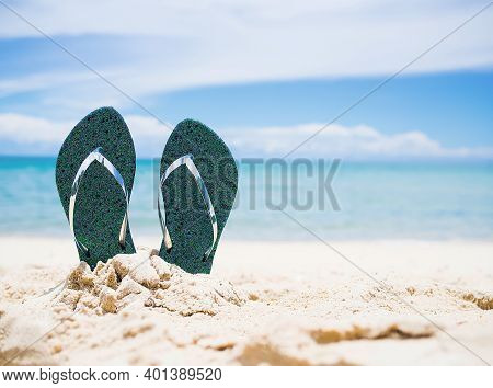 Flip Flops On Sand Beach With Blur Image Of Blue Sea And Blue Sky.  For Contains Articles About The