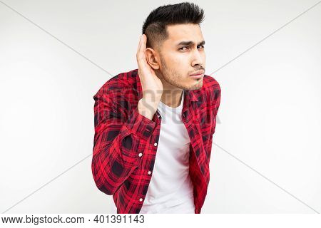 Brunette Guy In A Checkered Shirt Wide Open Eavesdrops On A Conversation On A White Studio Backgroun