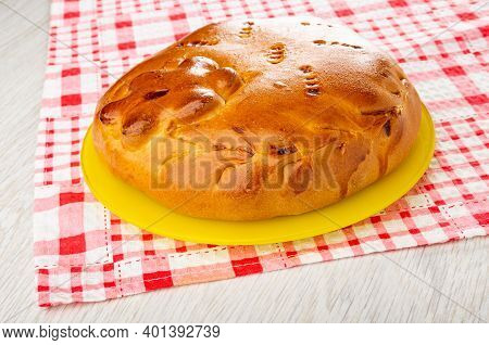 Homemade Savory Pie With Filling In Yellow Glass Plate On Checkered Napkin On Wooden Table