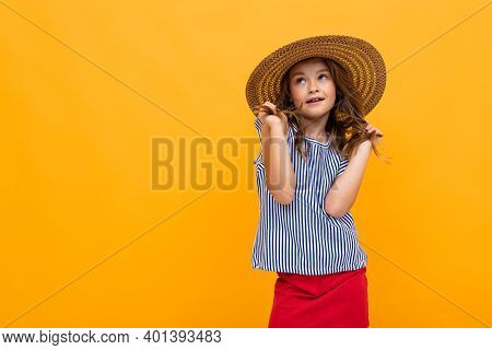 Young Fashionista Teenage Girl Flirts In A Straw Hat And Summer Blouse On A Yellow Background With C