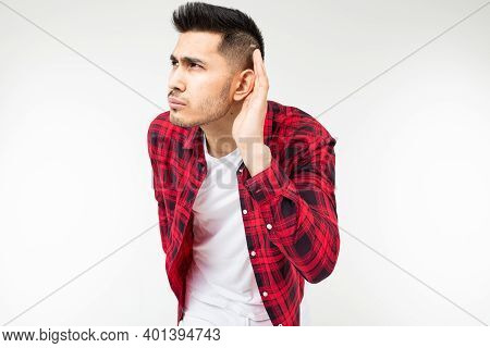 Brunette Man In A Checkered Shirt Wide Open Eavesdrops On A Conversation On A White Studio Backgroun