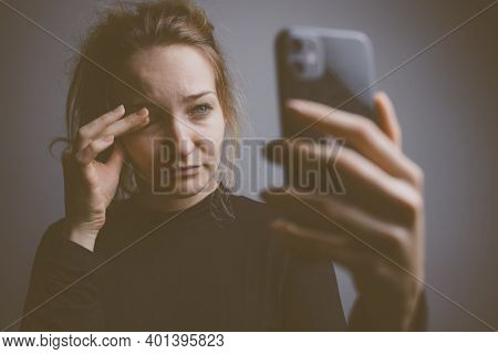 Young woman holding a phone, tired and exhausted, blue light straining her eyes, messing up her circadian rhytm