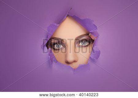 Woman with beautiful eyes and creative eye makeup looking through a hole in a sheet of purple paper so that only her eyes are visible