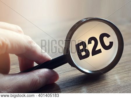 Businessman Holding A Magnifying Glass Abbreviation B2c. Business To Customer Concept.