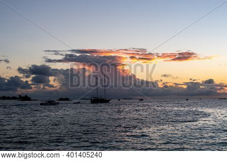 Wooden Ship Sailing With Cumulonimbus Thunderstorm Clouds And Sunset In The Background, Maldives.