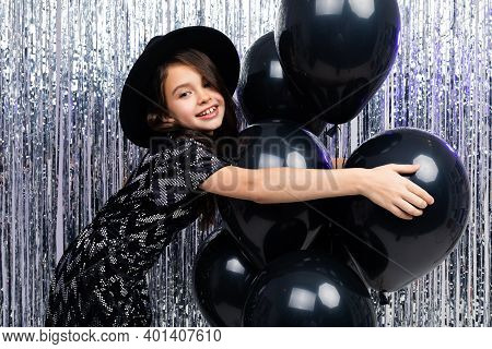 Attractive European Sunny Teenager Girl On Holiday On The Background Of Black Helium Balloons And Ti