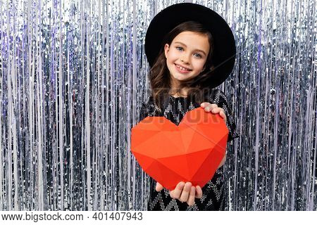 Smiling Cute Girl In A Festive Dress And Hat Holds A Red Paper Heart On A Shiny Background With Tins