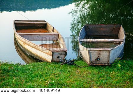 Idyllic Riverside With Wooden Boats . Green River Shore With Fishing Boats