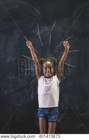 Beautiful Little Mixed Race Girl Standing In Front Of A Chalkboard In Classrom Excited And Happy Wit