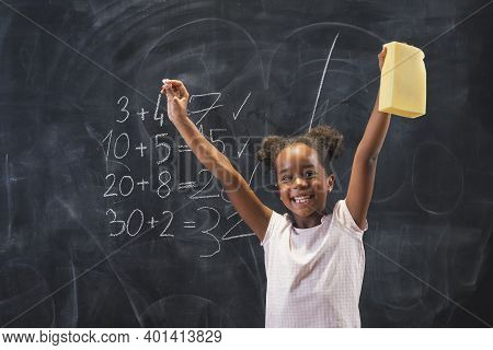 Beautiful Mixed Race Elementary School Girl Standing In Front Of A Chalkboard, Happy After Solving M