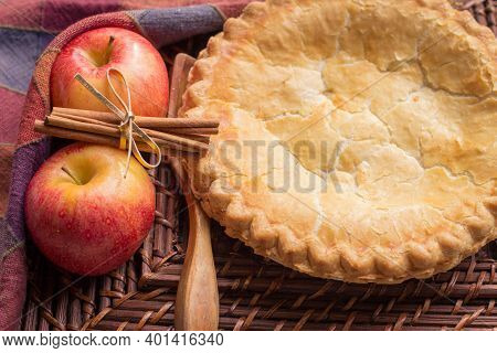 Homemade Apple Pie With A Flaky Crust, Surrounded By Apples And Fresh Cinnamon Sticks.