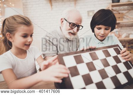 Grandfather, Grandson And Granddaughter At Home. Grandpa And Children Are Opening Chess Board.