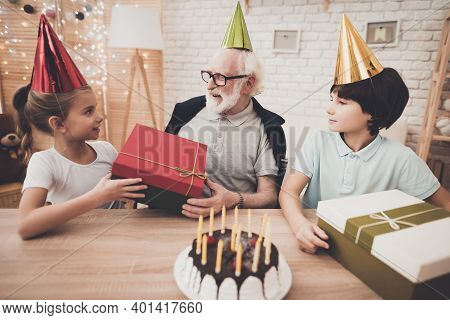 Grandfather, Grandson And Granddaughter At Home. Birthday Party.
