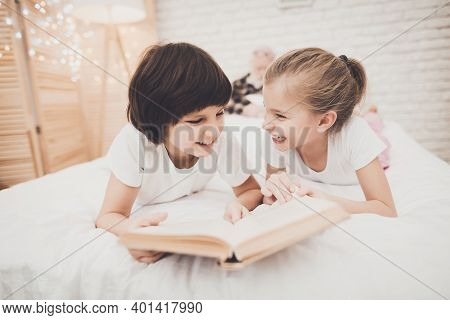Grandfather, Grandson And Granddaughter At Home. Children Are Reading Book While Grandpa Is Sleeping