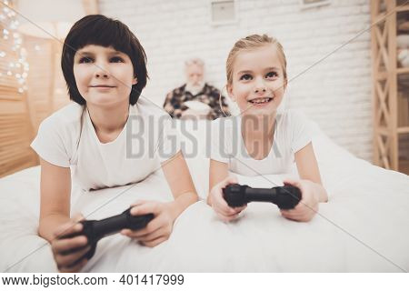 Grandfather, Grandson And Granddaughter At Home. Children Are Playing Video Games While Grandpa Is S