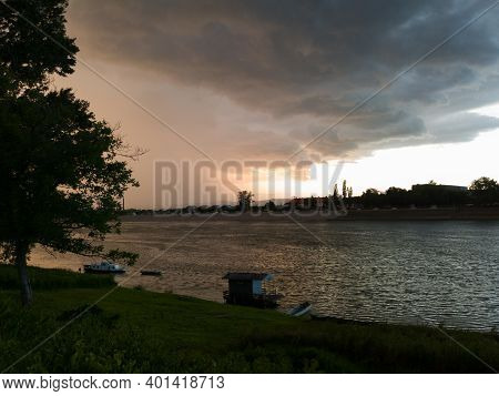 Storm Cumulonimbus Cloud With Heavy Rain Or Summer Shower, Severe Weather And Sun Glow Behind Rain.