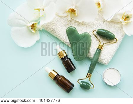 Face Massage Jade Roller With Cosmetic Product On Pastel Green Background